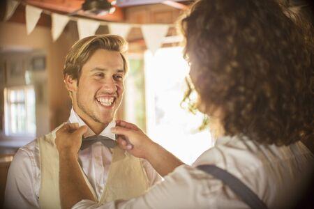 waistcoat: Bridegroom and best man preparing for wedding ceremony LANG_EVOIMAGES