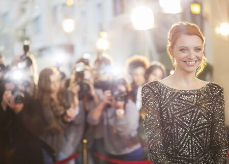 Smiling celebrity at event with photographing paparazzi in background LANG_EVOIMAGES