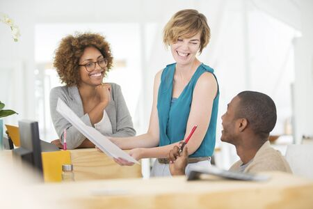 jamaican adult: Colleagues talking and smiling in office,holding documents LANG_EVOIMAGES