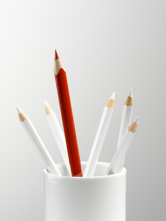 Tall red pencil in cup with smaller white pencils still life