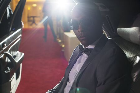 jamaican adult: Portrait of serious celebrity in sunglasses inside limousine arriving at red carpet event