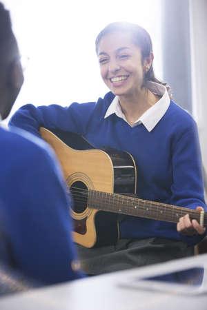 Sonriendo estudiante tocando la guitarra acústica