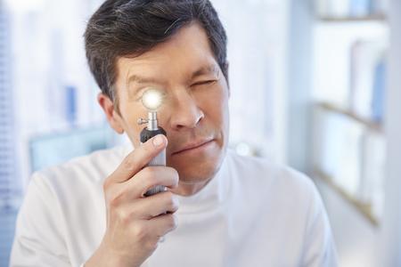 speculum: Man looking through illuminated speculum in laboratory