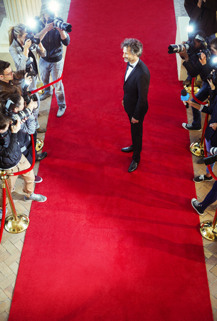 Celebrity being photographed by paparazzi photographers at red carpet event