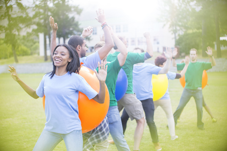 Teammates performing fitness ball team building activity
