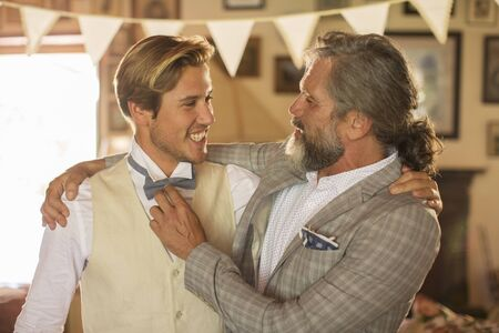 bridegrooms: Best man and bridegroom standing and embracing in domestic room LANG_EVOIMAGES