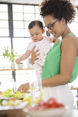 multi tasking: Woman with baby girl preparing meal in domestic kitchen