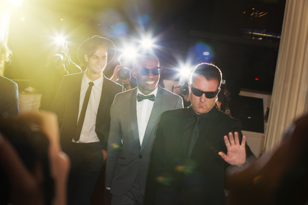 escorting: Bodyguard escorting celebrities arriving at event and being photographed by paparazzi