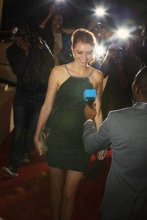 jamaican adult: Celebrity being interviewed and photographed by paparazzi photographers at red carpet event