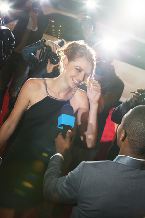 jamaican adult: Celebrity being interviewed and photographed by paparazzi at event