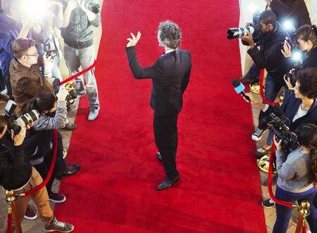 jamaican adult: Celebrity arriving at red carpet event and waving at photographing paparazzi