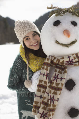 looking away from camera: Portrait of smiling woman with snowman