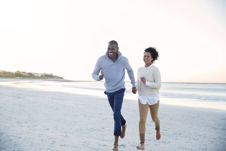 jamaican adult: Couple holding hands and running on beach