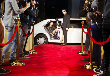roped: Bodyguard opening limousine for celebrity arriving at red carpet event