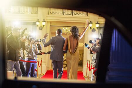 Celebrity couple arriving and waving to paparazzi photographers at red carpet event