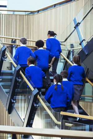 jamaican ethnicity: Rear view of group of pupils wearing blue school uniforms walking up stairs in school