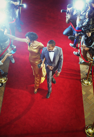Celebrity couple arriving at event waving and walking the red carpet LANG_EVOIMAGES