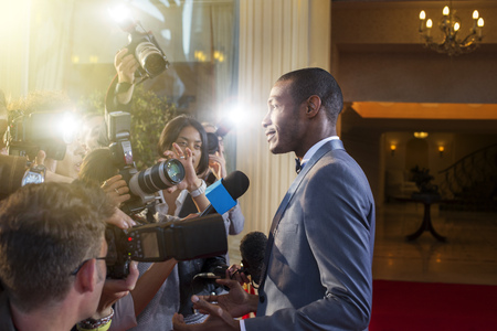 jamaican adult: Celebrity being interviewed and photographed by paparazzi at red carpet event