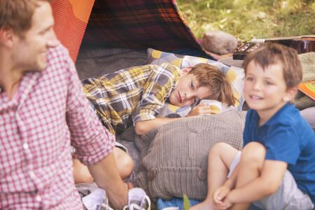 family: Father and sons smiling at camping tent