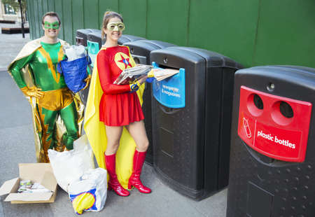 Superhero couple recycling on city sidewalk LANG_EVOIMAGES