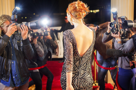 Celebrity leaving and being photographed by paparazzi photographers at red carpet event
