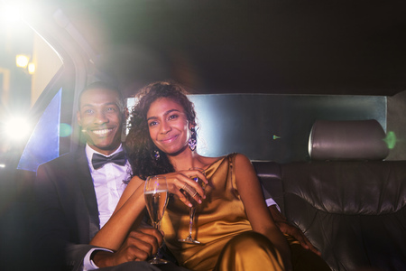 jamaican adult: Smiling celebrity couple drinking champagne inside limousine outside event