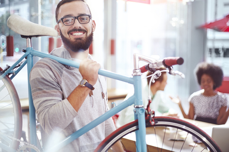 transportation: Smiling man carrying bicycle in cafe