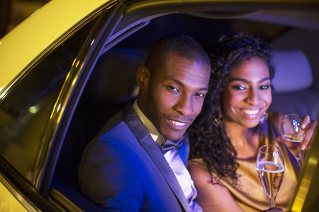 smile close up: Well-dressed couple drinking champagne inside limousine