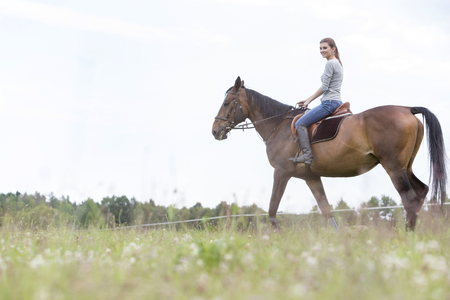 Woman horseback riding in rural field