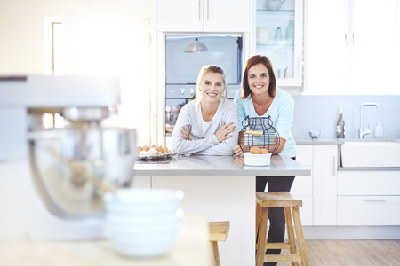 kitchen island: Portrait smiling women leaning on kitchen counter LANG_EVOIMAGES