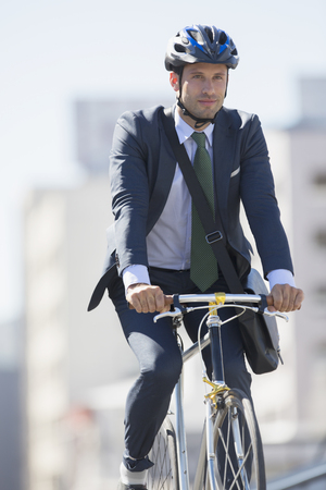 Businessman in suit commuting on bicycle with helmet LANG_EVOIMAGES