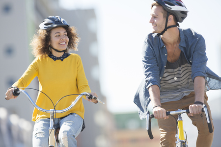 Young couple with helmets riding bicycles in city LANG_EVOIMAGES