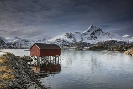 sund: Snow covered mountains behind fishing hut over lake, Sund, Lofoten Islands, Norway LANG_EVOIMAGES