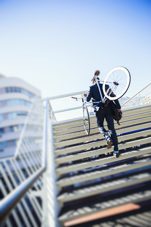 Businessman carrying bicycle up urban stairs under sunny blue sky LANG_EVOIMAGES