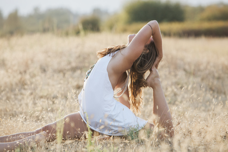 Boho woman in royal king pigeon pose in sunny rural field LANG_EVOIMAGES