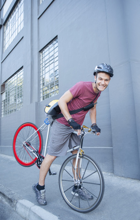 Portrait smiling bicycle messenger with helmet leaning forward on urban sidewalk LANG_EVOIMAGES