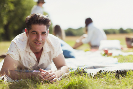 looking away from camera: Portrait smiling man laying on picnic blanket in sunny field LANG_EVOIMAGES