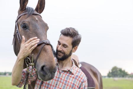 Smiling man hugging horse