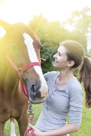 Smiling woman with horse LANG_EVOIMAGES