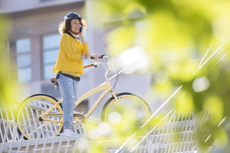 Smiling woman talking on cell phone on bicycle in city LANG_EVOIMAGES
