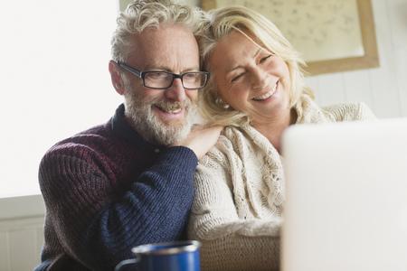 silver surfer: Smiling senior couple using laptop in kitchen LANG_EVOIMAGES