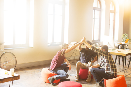 round chairs: Creative business people joining hands in circle in sunny office