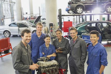 vocational high school: Portrait confident mechanics with car engine in auto repair shop