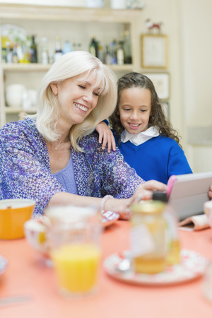 silver surfer: Grandmother and granddaughter using digital tablet at breakfast table