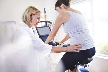 aligning: Physical therapist guiding woman's hips on stationary bike