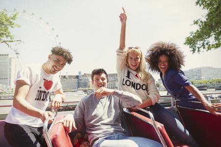 doubledecker: Portrait enthusiastic friends riding double-decker bus, London, United Kingdom