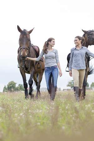 Women walking horses in rural field LANG_EVOIMAGES