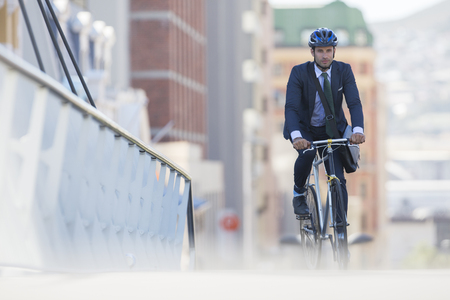 transportation: Businessman in suit and helmet riding bicycle in city LANG_EVOIMAGES