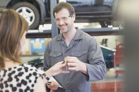 Mechanic taking keys from woman in auto repair shop