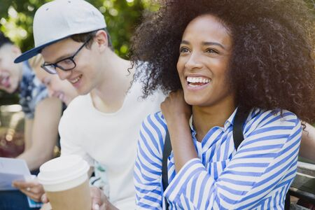 smile close up: Smiling woman with afro drinking coffee with friends outdoors